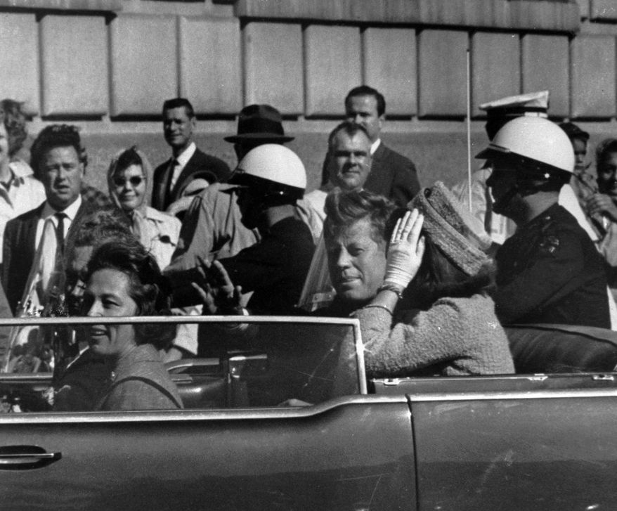 President John F. Kennedy is seen riding in motorcade approximately one minute before he was shot in Dallas, Tx., on Nov. 22, 1963.  In the car riding with Kennedy are Mrs. Jacqueline Kennedy, right, Nellie Connally, left, and her husband, Gov. John Connally of Texas.  (AP Photo)
