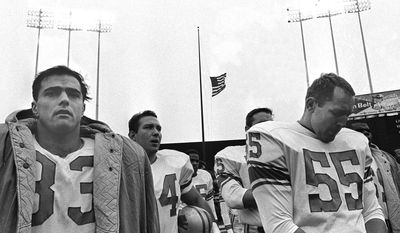 Detroit Lions' Nick Pietrosante (33), left, and Wayne Walker (55), right, stand during ceremonies honoring slain President John F. Kennedy, before a game between Detroit and the Minnesota Vikings at Metropolitian Stadium in Minneapolis, in this Nov. 24, 1963 photo. (AP Photo)