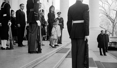 Jacqueline Kennedy and her two children, John Jr. and Caroline stand at the top steps of the Executive Mansion as the body of President John F. Kennedy is carried from the Executive Mansion to lie in state at the Capitol, Nov. 24, 1963.   (AP Photo)