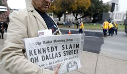Carlos Flores holds a copy of the Dallas Morning News as work crews finish up street work on Dealey Plaza in Dallas,  Thursday, Nov. 21, 2013.  Loose gatherings of the curious and conspiracy-minded at Dallas' Dealey Plaza have marked past anniversaries of the assassination of President John F. Kennedy. But for the 50th anniversary, the city of Dallas has planned a solemn ceremony Friday in the plaza he was passing through when shots rang out. There will be brief remarks by the mayor and the tolling of church bells.  (AP Photo/LM Otero)