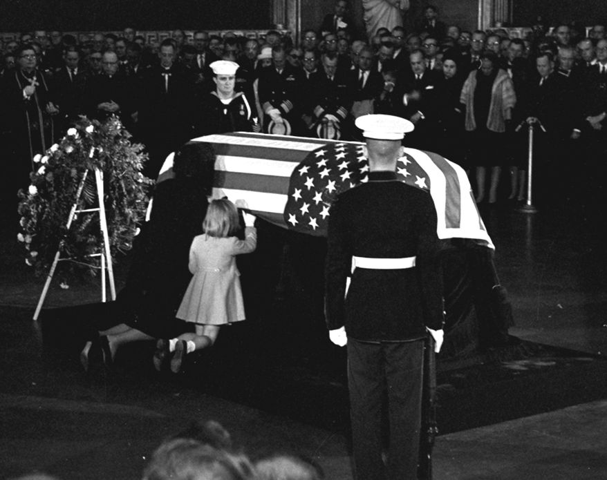 FILE - In this Sunday, Nov. 24, 1963 file photo, Jacqueline Kennedy kisses the casket of her husband, President John F. Kennedy, lying in state in the rotunda of the U.S. Capitol in Washington, accompanied by their daughter Caroline, kneeling alongside. (AP Photo/Henry L. Griffin, File)