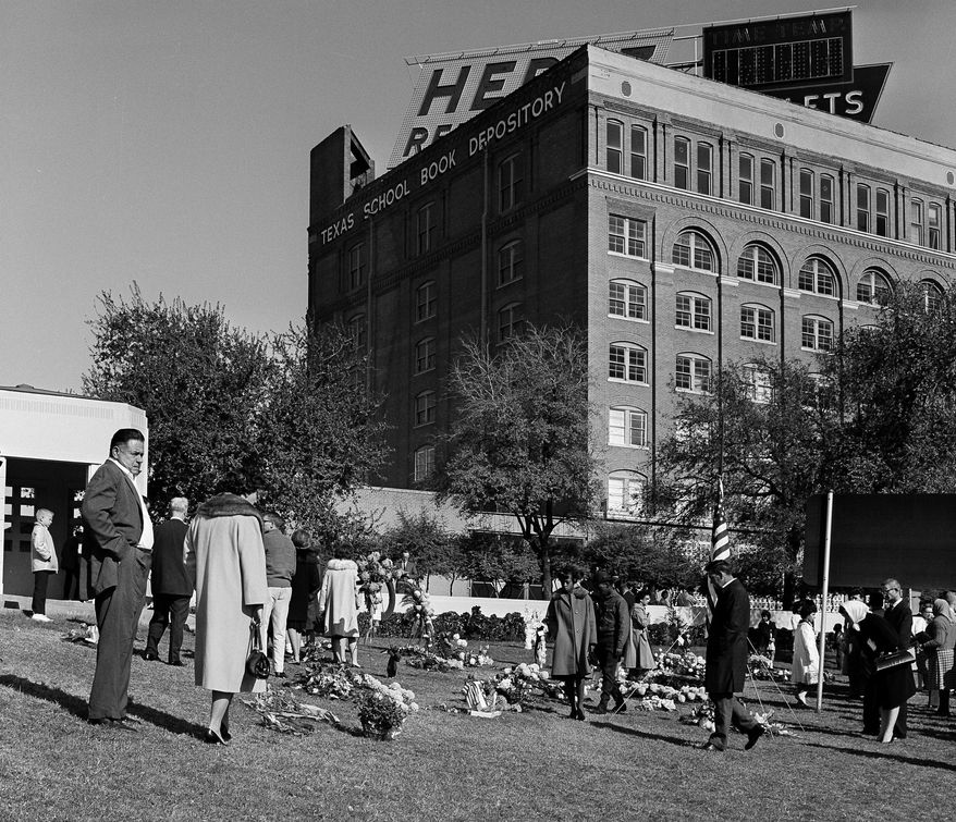 FILE - In this November 1963 file photo, mourners leave flowers on the lawn near the Texas Book Depository after the assassination of President John F. Kennedy in Dallas. (AP Photo/File)