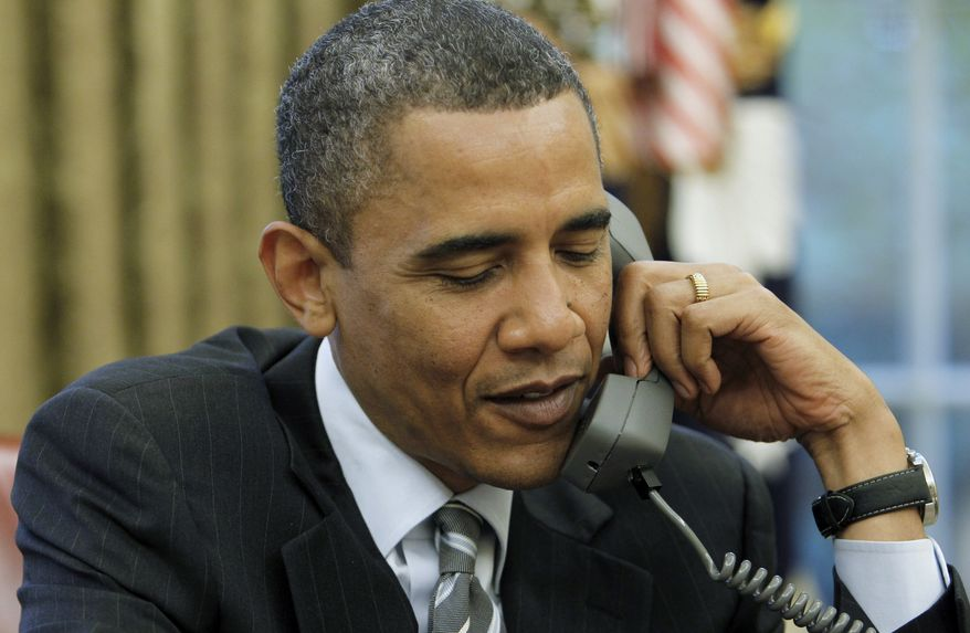 FILE - This May 11, 2010 file photo by an Associated Press photographer shows President Barack Obama talking on the phone with British Prime Minister David Cameron, in the Oval Office of the White House in Washington. Twice from 2008-2013, White House-based photographers have been given access to President Obama working at his desk alone in the Oval Office. (AP Photo/Charles Dharapak, File)
