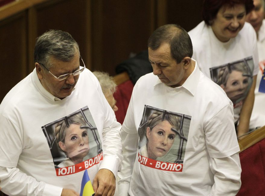 Opposition lawmakers wear shirts emblazoned with a photo of jailed former Premier Yulia Tymoshenko during a session of the Ukrainian parliament in Kiev on Friday, Nov. 8, 2013. (AP Photo/Sergei Chuzavkov)