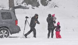 Chris Calma (left) of Rancho Cucamonga, Calif., runs to take a picture with his family in the snow after setting up his camera on self-timer mode in Wrightwood, Calif., on Friday, Nov 22, 2013. (AP Photo/The Victor Valley Daily Press, David Pardo)