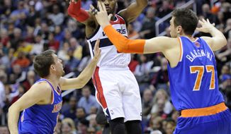 Washington Wizards point guard John Wall, center, passes the ball against New York Knicks power forward Andrea Bargnani (77), of Italy, and Beno Udrih, left, of Slovenia, during the second half of an NBA basketball game on Saturday, Nov. 23, 2013, in Washington. The Wizards won 98-89. (AP Photo/Nick Wass)