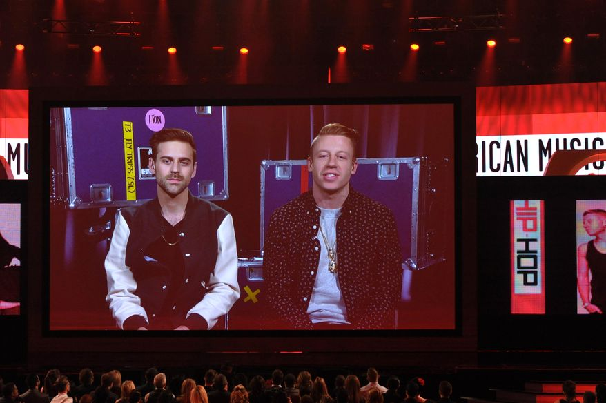 """Macklemore (right) and Ryan Lewis accept the award for favorite album-rap/hip-hop for """"The Heist"""" via satellite from Miami during the American Music Awards at the Nokia Theatre L.A. Live on Sunday, Nov. 24, 2013, in Los Angeles. (John Shearer/Invision/AP)"""