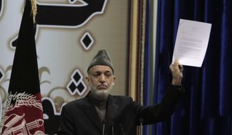 Afghan President Hamid Karzai holds a copy of a weekly security report during the last day of the Loya Jirga in Kabul, Afghanistan, on Sunday, Nov. 24, 2013. Mr. Karzai said he won't immediately sign a security deal with the United States, ignoring a recommendation by the assembly of Afghan elders and leaders that he do so by the end of the year. (AP Photo/Rahmat Gul)