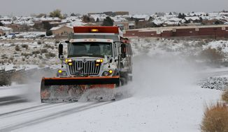 A Department of Transportation plow and sanding truck heads up Paseo del Norte in Albuquerque, N.M., Sunday, Nov. 24, 2013, after a winter storm hit New Mexico over the weekend making driving difficult. The large storm already blamed for at least eight deaths in the West slogged through Oklahoma, Texas, New Mexico and other parts of the southwest Sunday as it slowly churned east ahead of Thanksgiving. (Associated Press/Albuquerque Journal, Jim Thompson)