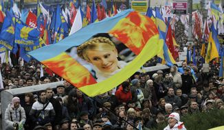 Demonstrators hold up a flag with the face of jailed former Ukrainian Prime Minister Yulia Tymoshenko during a protest in Kiev on Sunday, Nov. 24, 2013. Tens of thousands of demonstrators marched through the Ukrainian capital to demand that the government reverse course and sign a landmark agreement with the European Union in defiance of Russia. The protest was the biggest Ukraine has seen since the peaceful 2004 Orange Revolution, which overturned a fraudulent presidential election result and brought a Western-leaning government to power. (AP Photo/Sergei Chuzavkov)