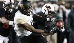 Oklahoma State linebacker Joe Mitchell (29) breaks up a pass intended for Baylor wide receiver Antwan Goodley (5) in the fourth quarter of an NCAA college football game in Stillwater, Okla., Saturday, Nov. 23, 2013. Oklahoma State won 49-17. (AP Photo/Sue Ogrocki)