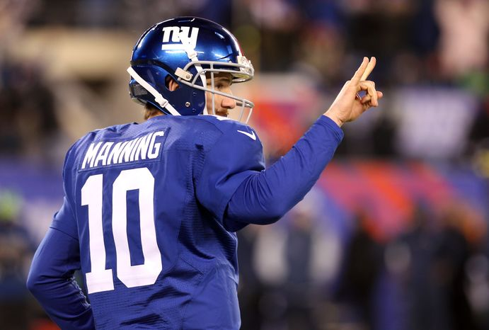 New York Giants quarterback Eli Manning gestures toward the bench signaling for a two-point conversion play after a touchdown during the second half of an NFL football game against the Dallas Cowboys, Sunday, Nov. 24, 2013, in East Rutherford, N.J. The Cowboys won 24-21. (AP Photo/Peter Morgan)