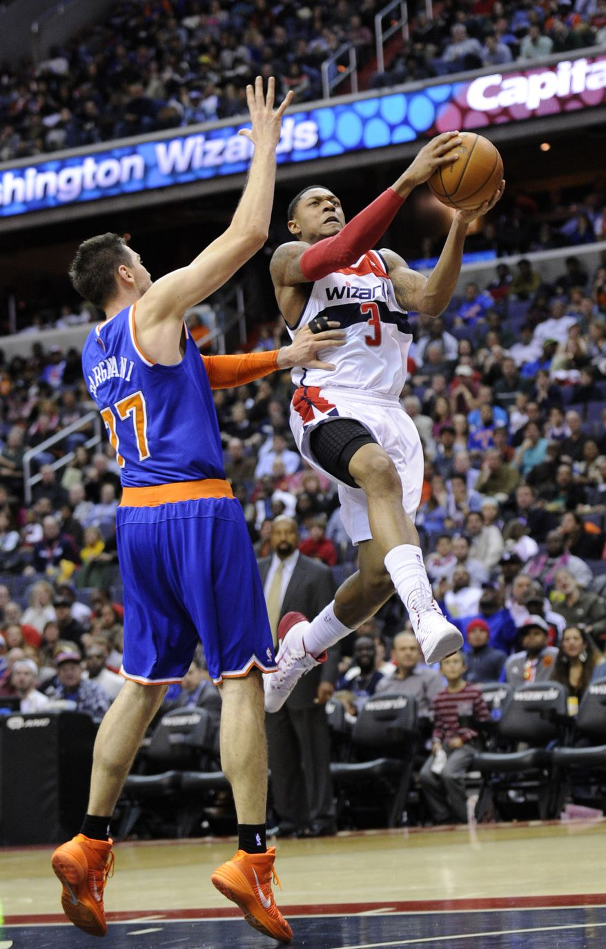 Washington Wizards guard Bradley Beal (3) goes to the basket against New York Knicks forward Andrea Bargnani (77), of Italy, during the second half of an NBA basketball game, Saturday, Nov. 23, 2013, in Washington. Bargnani was called for a foul on the play. The Wizards won 98-89. (AP Photo/Nick Wass)