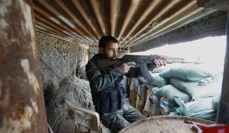 In this photo taken Friday, Nov. 22, 2013, a Shiite fighter from a group called the Hussein Brigade fires his weapon during clashes with members of Sunni-dominated Free Syrian Army rebels in the town of Hatita, in the countryside of Damascus, Syria. (AP Photo/Jaber al-Helo)