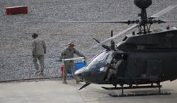 Soldiers from the 2nd Squadron, 17th Cavalry Regiment, 101st Airborne Division at Fort Campbell, Ky., reload rockets onto a helicopter during a training exercise on Friday, Nov. 22, 2013. The unit was able to continue flying training missions during the government shutdown and budget cutbacks by purchasing spare parts for helicopters over the summer before budget restrictions took effect. (AP Photo/Brett Barrouquere)