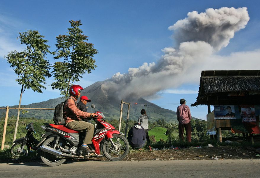 Villagers watch Mount Sinabung spewing volcanic ash into in Tiga Pancur, North Sumatra, Indonesia, Monday, Nov. 25, 2013. Powerful bursts of hot ash and gravel erupted from the rumbling volcano in western Indonesia Monday, a day after authorities had raised the volcano's alert status to the highest level. (AP Photo/Binsar Bakkara)