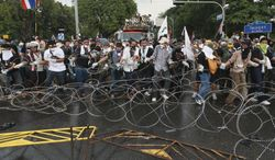 Anti-government protesters try to remove barbed wire set up by Thai riot police during a rally in Bangkok, Thailand, Monday, Nov. 25, 2013. Bangkok braced for major disruptions Monday as a massive anti-government march fanned out to 13 locations in a growing bid to topple the government of Prime Minister Yingluck Shinawatra. (AP Photo/Wason Wanitchakorn)