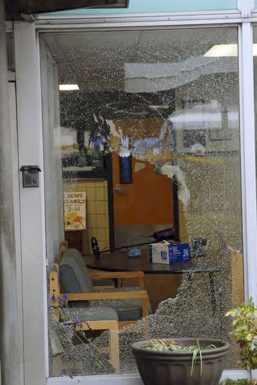 """This image contained in the """"Appendix to Report on the Shootings at Sandy Hook Elementary School and 36 Yogananda St., Newtown, Connecticut On December 14, 2012"""" and released Monday, Nov. 25, 2013, by the Danbury, Conn., State's Attorney shows a scene outside the entrance to Sandy Hook Elementary School in Newtown, Conn. Adam Lanza opened fire inside the school killing 20 first-graders and six educators before killing himself as police arrived. (AP Photo/Office of the Connecticut State's Attorney Judicial District of Danbury)"""