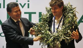 World Chess Federation President Kirsan Ilyumzhinov, left, presents new world chess champion Magnus Carlsen of Norway with a laurel wreath at the award presentation ceremony of the FIDE World Chess Championship in Chennai, India, Monday, Nov. 25, 2013. Carlsen won the match in Chennai Friday beating Indian title holder Viswanathan Anand. (AP Photo/Arun Sankar K.)