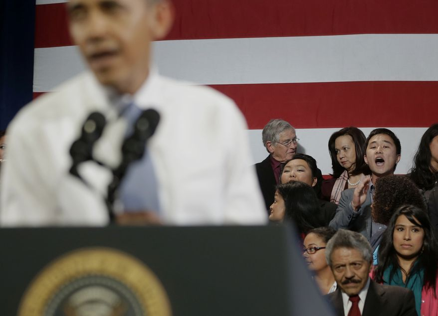 "President Barack Obama, left, has his speech interrupted by Ju Hong, right on stage, who heckled him about anti-deportation policies, Monday, Nov. 25, 2013, at the Betty Ann Ong Chinese Recreation Center in San Francisco. The young man shouted about his family being separated for Thanksgiving, and said Obama should use his executive power to stop this. ""Stop deportations, yes we can,"" the man and other people chanted. The Obama stopped Secret Service agents who tried to remove the protesters. (AP Photo/Pablo Martinez Monsivais)"