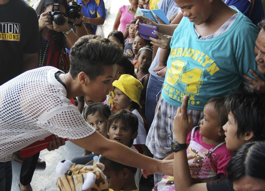 In this photo released by the Philippine Air Force, Grammy-winning singer Alicia Keys, left, touches a typhoon survivor as she visits the Villamor Air Base in suburban Pasay, south of Manila, Philippines, Monday Nov. 25, 2013. Keys visited the air force base to bring cheer to hundreds of evacuees from eastern Philippine provinces wracked by Typhoon Haiyan earlier this month. (AP Photo/Philippine Air Force)