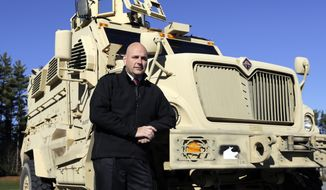 Warren County, N.Y., Undersheriff Shawn Lamouree poses in front of the department's mine-resistant ambush-protected vehicle, or MRAP, on Wednesday, Nov. 13, 2013, in Queensbury, N.Y. (AP Photo/Mike Groll)