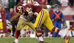 Washington Redskins running back Alfred Morris is stopped by San Francisco 49ers outside linebacker Ahmad Brooks during the second half of an NFL football game in Landover, Md., Monday, Nov. 25, 2013. (AP Photo/Mark Tenally)