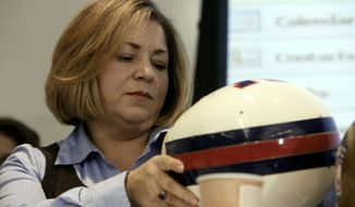 "Rep. Linda Sanchez, D-Calif., views a older NFL football helmet during a hearing titled ""Legal Issues Relating to Football Head Injuries, Part II"" in Detroit, Monday, Jan. 4, 2010. (AP Photo/Paul Sancya) ** FILE **"