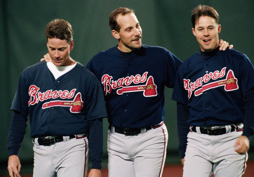 Atlanta Braves pitchers from left, Tom Glavine, John Smoltz and Greg Maddux have a moment together before their game with Philadelphia Phillies at Veterans Stadium, on Oct. 6, 1993.(AP Photo/Doug Mills)