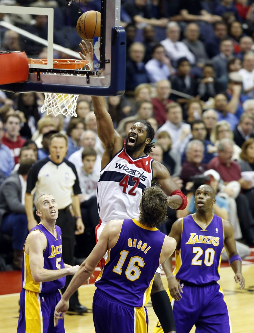 Washington Wizards forward Nene (42), from Brazil, shoots between Los Angeles Lakers guard Steve Blake (5), center Pau Gasol (16), from Spain, and guard Jodie Meeks (20) in the second half of an NBA basketball game Tuesday, Nov. 26, 2013, in Washington. Nene had 30 points and the Wizards won 116-111. (AP Photo/Alex Brandon)