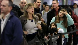Travelers wait in line to board a flight at LaGuardia Airport in New York, Tuesday, Nov. 26, 2013. A winter storm system that hit parts of Arkansas, Oklahoma and Texas swept toward the densely populated East Coast on Tuesday, threatening to disrupt the plans of travelers ahead of the long Thanksgiving holiday weekend. (AP Photo/Seth Wenig)
