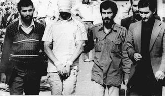 ** FILE ** In this Nov. 9, 1979, file photo, one of the hostages being held at the U.S. Embassy in Tehran is displayed to the crowd, blindfolded and with his hands bound, outside the embassy. Fifty-two of the hostages endured 444 days of captivity. Former Iranian hostages had varied reactions to the news of the nuclear deal between the U.S. and Iran in what is being billed as a trust-building agreement designed to yield a more comprehensive deal six months from now. (AP Photo/File)