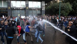 Egyptian police fire water cannons to disperse a protest by secular anti-government activists in Cairo, Tuesday, Nov. 26, 2013, the security forces' first implementation of a controversial new law forbidding protests held without a permit from authorities. (AP Photo/Ahmed Gomaa)