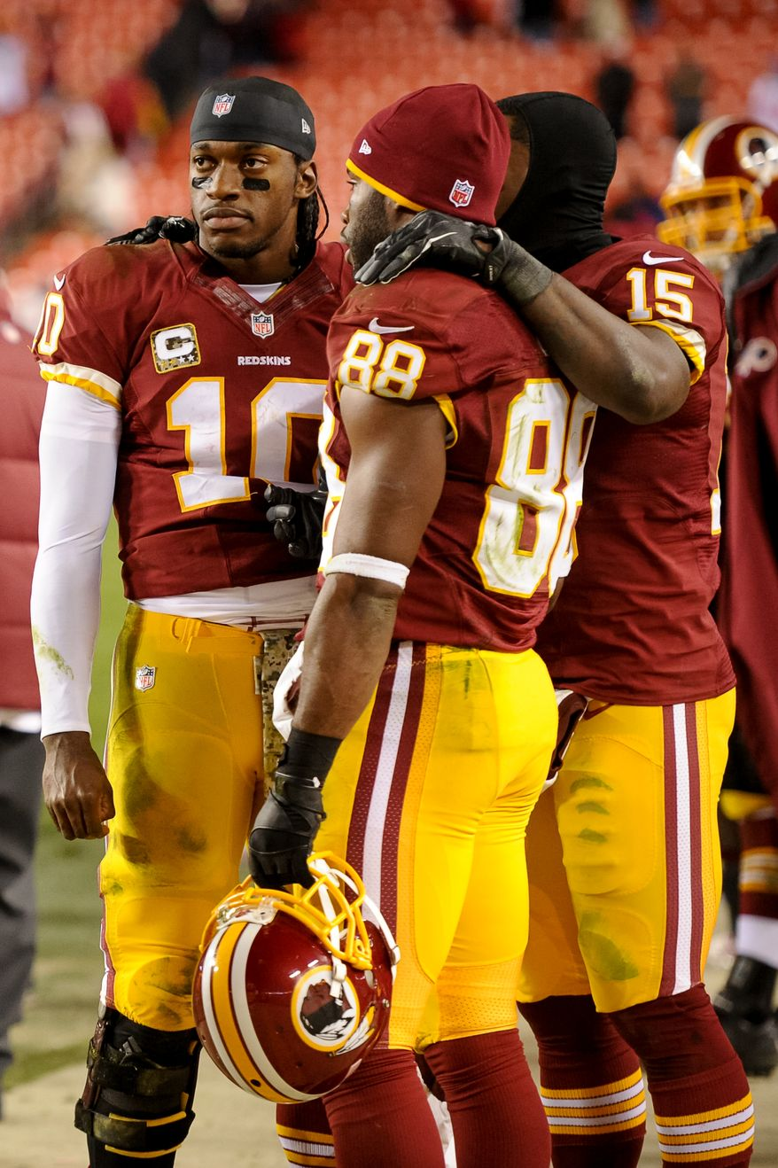 Washington Redskins quarterback Robert Griffin III (10), left, talks with Washington Redskins wide receiver Pierre Garcon (88) and Washington Redskins wide receiver Josh Morgan (15) on the sideline late in the fourth quarter as the Washington Redskins go on to lose to the San Francisco 49ers 27-6 in Monday Night Football at FedExField, Landover, Md., Tuesday, November 26, 2013. (Andrew Harnik/The Washington Times)