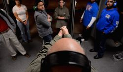 Participants in a handgun qualification license class listen to Dick Chiapparoli as he gives firing instructions during the live-shooting portion of the class at Gilbert's Indoor Shooting Range in Rockville. Maryland residents need to take the class before they can buy a gun under a law passed this year. (andrew harnik/the washington times)