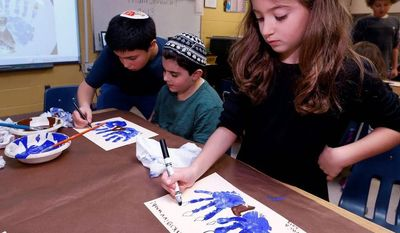 Second-grader Talia Begres, 7, works on a menurkey, a paper-and-paint mash-up of a menorah and a turkey at Hillel Day School in Farmington Hills, Mich., one way for Jews in the U.S. to deal with a quirk of the calendar that overlaps Thanksgiving with the start of Hanukkah. (Associated Press)