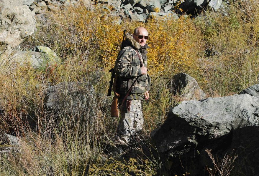 In this sept. 2010 photo released on Saturday, Oct. 30, 2010, Russian Prime Minister Vladimir Putin carries a hunting rifle during his trip in Ubsunur Hollow in the Siberian Tyva region (also referred to as Tuva), on the border with Mongolia, Russia. (AP Photo/RIA Novosti, Alexei Druzhinin, Pool)