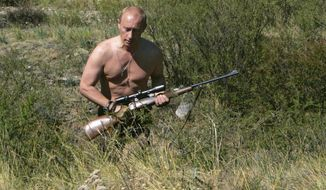 FILE - In this Sept. 2010 photo released on Saturday, Oct. 30, 2010, then Russian Prime Minister Vladimir Putin carries a hunting rifle during his trip in Ubsunur Hollow in the Siberian Tyva region (also referred to as Tuva), on the border with Mongolia, Russia.   Vladimir Putin turns 60-years old on Sunday, Oct. 7, 2012, and has recently sought to demonstrate his youthful vigor by many personal endeavors, but while he has shown creativity in his action-man stunts, the Russian president seems surprisingly vulnerable to the vagaries of oil prices. (AP Photo/RIA Novosti, Dmitry Astakhov, Government Press Service, file)