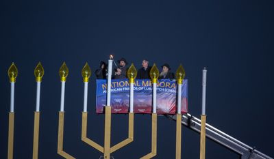 Rabbi Abraham Shemtov (left) lights a giant Menorah in front of the White House during a special Jewish Event, in Washington, DC., Wednesday, November 27, 2013.  (Andrew S Geraci/The Washington Times)