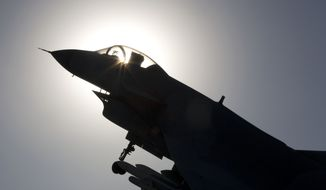 The replica of a Chinese made fighter jet is silhouetted against the sun in Beijing, China, Wednesday, Nov. 27, 2013.  China said Wednesday it had monitored two unarmed U.S. bombers that flew over the East China Sea in defiance of Beijing's declaration it was exercising greater military control over the area. (AP Photo/Ng Han Guan)