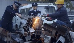 """Municipal officers observe as a worker breaks down open-air barbecues confiscated in the past three months in the Xicheng district in Beijing on Tuesday, Nov. 26, 2013. Authorities in the Chinese capital have destroyed more than 500 open-air barbecues """"to cut PM2.5,"""" the tiny particulate matter in the air that can enter deep into the lungs. (AP Photo)"""