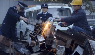"Municipal officers observe as a worker breaks down open-air barbecues confiscated in the past three months in the Xicheng district in Beijing on Tuesday, Nov. 26, 2013. Authorities in the Chinese capital have destroyed more than 500 open-air barbecues ""to cut PM2.5,"" the tiny particulate matter in the air that can enter deep into the lungs. (AP Photo)"