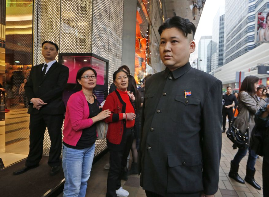 A 35-year-old, a Hong-Kong born Australian musician Howard, dressed as North Korean leader Kim Jong-un, walks past the Louis Vuitton store in a Hong Kong shopping district, Wednesday Nov. 27, 2013. Howard claims to be the world's first professional Kim Jong-un impersonator. (AP Photo/Kin Cheung)