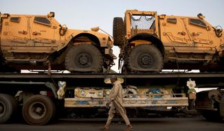 A Pakistani walks past a supply truck carrying military vehicles for NATO troops in Afghanistan at a terminal in Karachi, Pakistan, on Tuesday, Nov. 26, 2013. Supply trucks remained stuck in Pakistan as concern lingered about demonstrators seeking to stop the vehicles in protest of U.S. drone strikes, Pakistani transportation officials said. (AP Photo/Shakil Adil)
