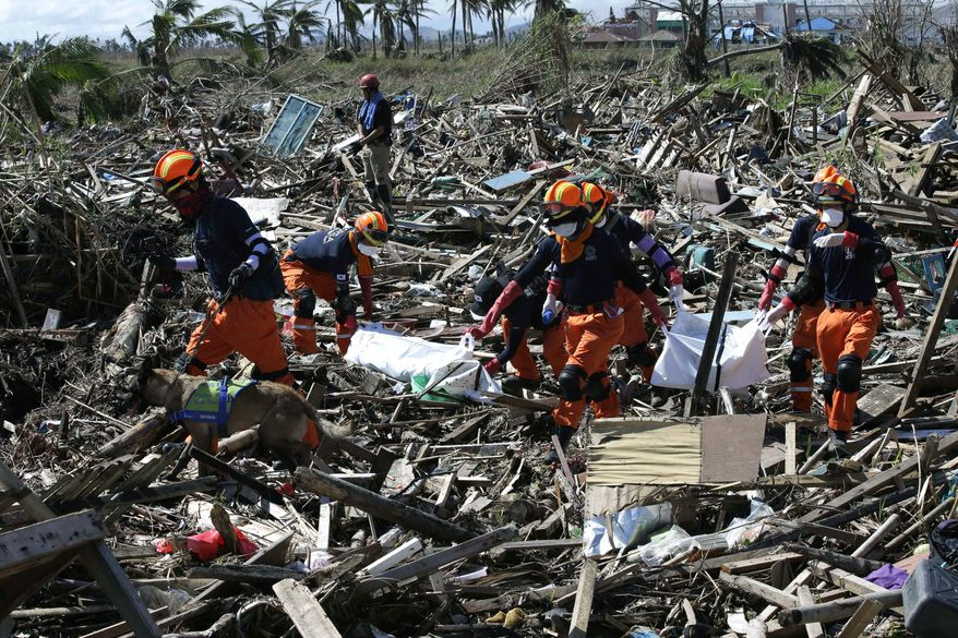 Members of a South Korean Disaster Team carry the bodies of typhoon victims Wednesday, Nov. 27, 2013, in Tacloban city, Leyte province in central Philippines. Typhoon Haiyan, one of the most powerful storms on record, hit the country's eastern seaboard Nov. 8, leaving a wide swath of destruction.  (AP Photo/Bullit Marquez)