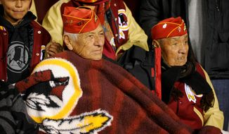 World War II Navajo code talkers stay warm along the sideline before being honored by the Redskins as the Washington Redskins play the San Francisco 49ers in Monday Night Football at FedExField, Landover, Md., Monday, November 25, 2013. (Andrew Harnik/The Washington Times)