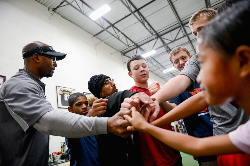 """Eddie Mason (left) huddles with young players at Mase Training, his football training facility. Regarding concussions, he said, """"I think there's a way we can really head this issue off and bring safety back to the game, but it's going to take time."""" (andrew harnik/the washington times)"""