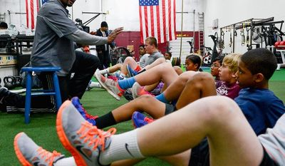 EARLY STUDY: Former Washington Redskins linebacker Eddie Mason works with young students at Mase Training in Sterling, Va. He advocates an approach that teaches the young the fundamentals of football without pads and full contact until they are in high school. (ANDREW HARNIK/THE WASHINGTON TIMES)