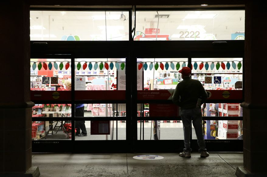 A shopper who declined to give his name waits outside a Kmart store for it to open on Thursday, Nov. 28, 2013, in Anaheim, Calif.  Instead of waiting for Black Friday, which is typically the year's biggest shopping day, more than a dozen major retailers are opening on Thanksgiving day this year. (AP Photo/Jae C. Hong)