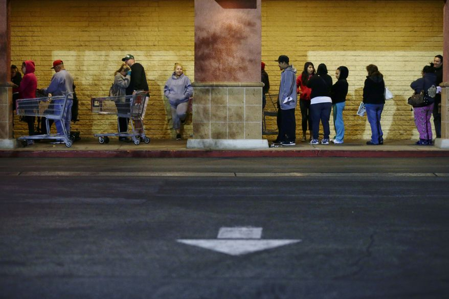 Shoppers wait outside a Kmart store for it to open on Thursday, Nov. 28, 2013, in Anaheim, Calif. Instead of waiting for Black Friday, which is typically the year's biggest shopping day, more than a dozen major retailers are opening on Thanksgiving day this year. (AP Photo/Jae C. Hong)